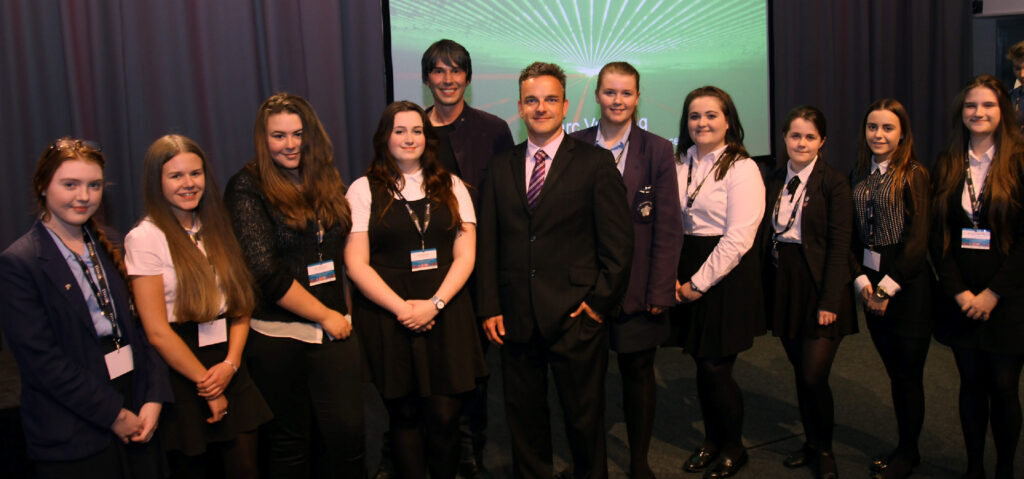 Prof. Brian Cox and Prof. Carsten Welsch with students at the Symposium.