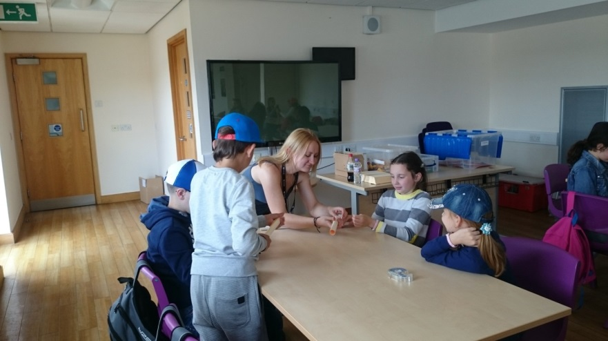 Alex helping children from the Chernobyl children's project build and design paper rockets.