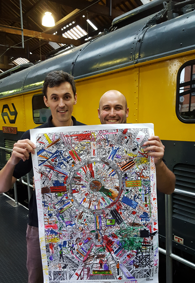 Organisers Dr's Chris Edmonds (University of Liverpool) and Rob Appleby (University of Manchester) proudly show the results of the ATLAS colouring activity. Dr Lee Jones (ASTeC) was more reluctant to take credit.